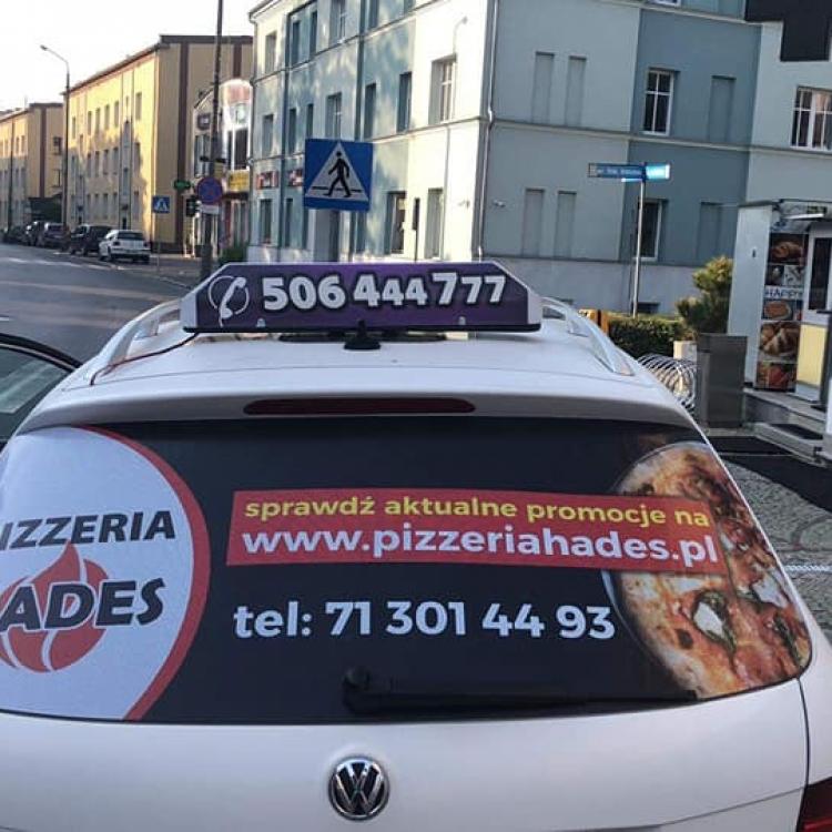 Reklama pizzeri Hades na tylnej szybie naszej taksówki