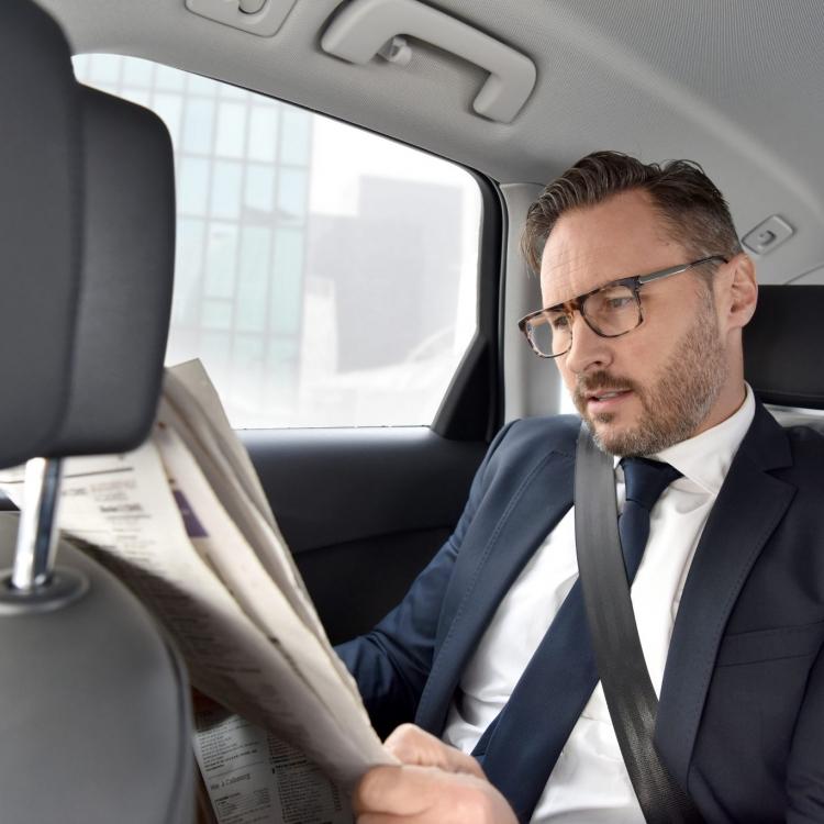 Mężczyzna czyta gazetę w taksówce
